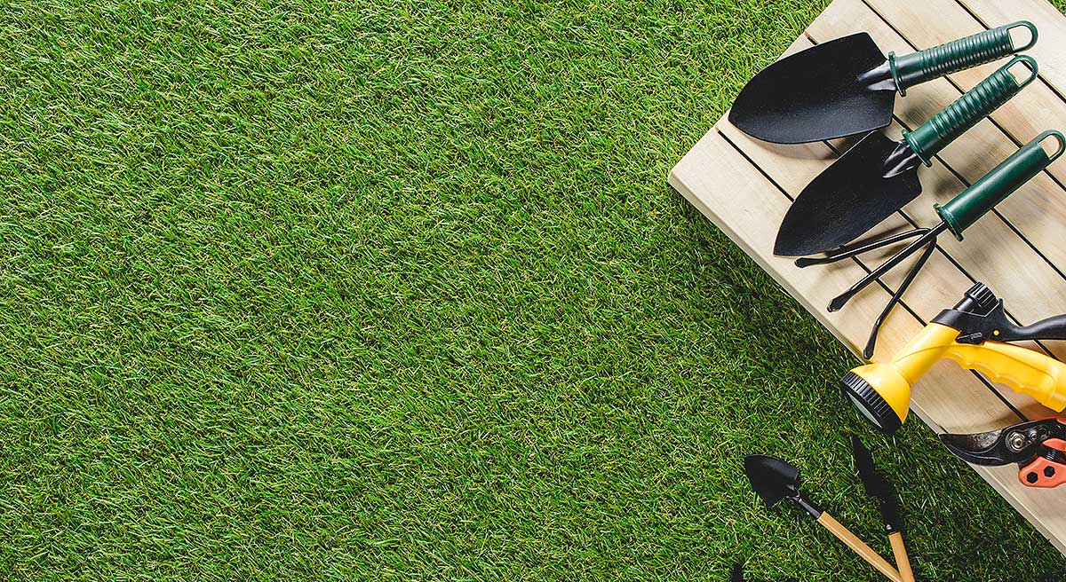 top view of gardening tools and equipment on grass - synthetic grass installers